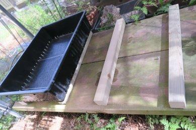 底に防草網を敷いた苗箱、下に防腐処理した角棒を足に