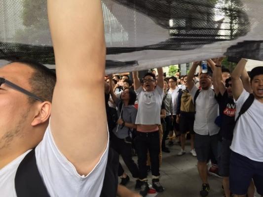 日の丸を踏みつぶしながら「安倍やめろ」の大きな幕を掲げた少数のプロ市民活動家1