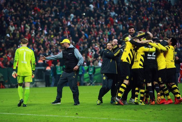Jurgen Klopp consoles Manuel Neuer while his Borussia Dortmund team celebrate victory over Bayern Munich