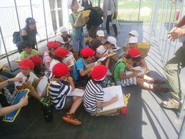 【写真】農園主に質問をする男の子とその内容をノートに書き込む小学2年生の生徒さん