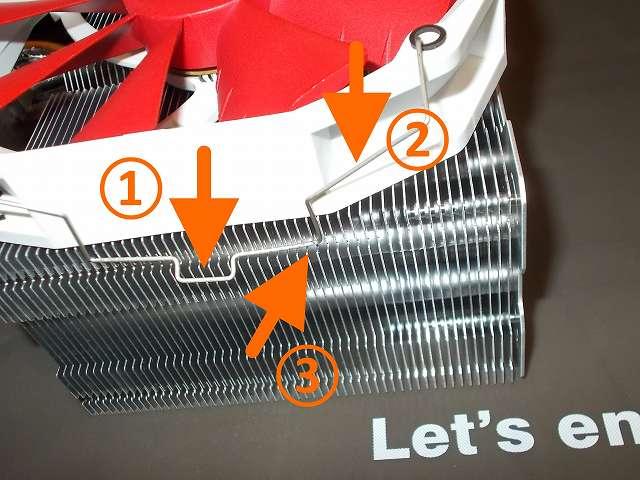 REEVEN OURANOS RC-1401 サイドフロー型 CPU クーラーに Phanteks PH-F140HP_RD 140mm口径 PWM 汎用ファン装着テスト、Phanteks PH-F140HP_RD ネジ穴に REEVEN OURANOS RC-1401 のファンクリップを取り付けて、① ファンクリップのワイヤー中央出っ張り部分を指で押し下げながら、② ワイヤー中央出っ張りとワイヤー末端の中間にある斜めになっているワイヤーを指で押し下げながら、③ CPU クーラーのヒートシンク側にある溝にワイヤーを押し込んで引っかける、片側のワイヤーも同じように押し下げてワイヤーをヒートシンク溝に押し込んで引っかける